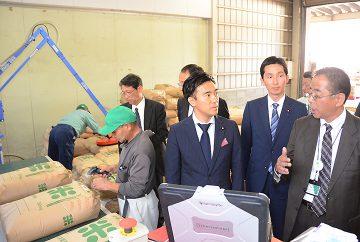 コメの全量全袋検査を視察する矢倉政務官と真山氏=26日 福島・川俣町