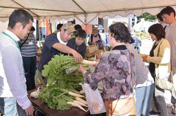 地域のまつりで、自作の野菜などを販売する塾生ら=16日 山形・鶴岡市