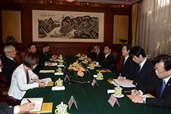 (4)中日友好協会の唐家セン会長(左端)と会談する山口代表(右から3人目)ら=14日