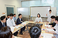 薬物依存症の治療プログラムを模擬体験する新妻、矢倉の両氏=10日 都内