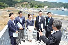 復興へ工事が進む町の現状を視察する樋口局長(左から2人目)ら=29日 宮城・女川町