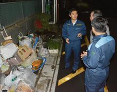 流された生活用具の前で、浸水被害の状況を聞く矢倉氏=11日 さいたま市岩槻区