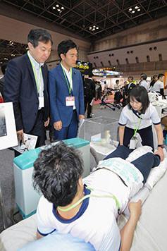 自動排泄処理ロボットの試作品を視察する輿水、矢倉の両氏=8日 都内
