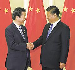 習近平国家主席と握手を交わす山口代表=15日 北京・人民大会堂